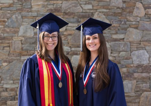 Former physics students Wren Gregory and Ashlyn Rickard in graduation attire.